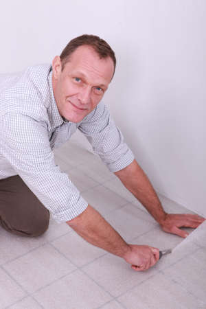 floor covering: craftsman covering tiled floor Stock Photo
