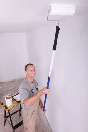 Decorator using a roller extension to paint a ceiling white photo