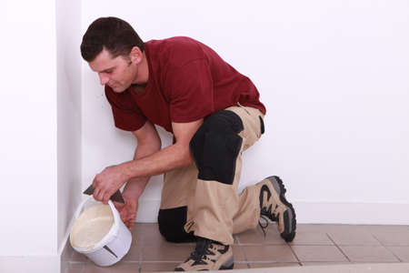 tile adhesive: Man pouring tile adhesive over an old floor