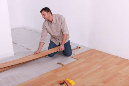 Man renovating the floor with wood panels Stock Photo