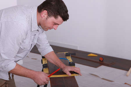 Man laying a floor and measuring a piece of wood photo
