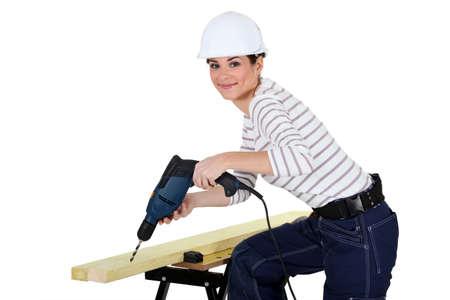 Woman drilling wood photo