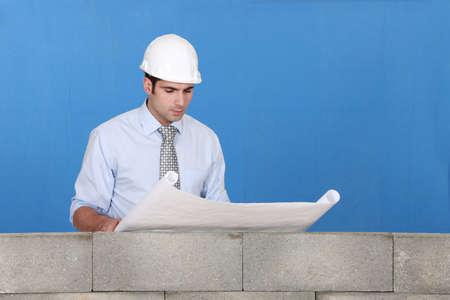 inspect: Engineer inspecting a construction blueprint