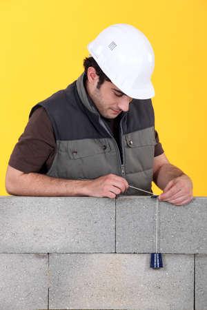 plumb: A mason using a plumb bob to check his wall.