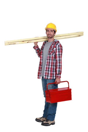 Carpenter carrying planks of wood and tool-box photo