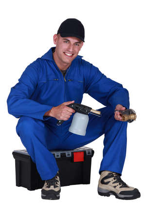 Man sitting on a toolbox with a blowtorch photo