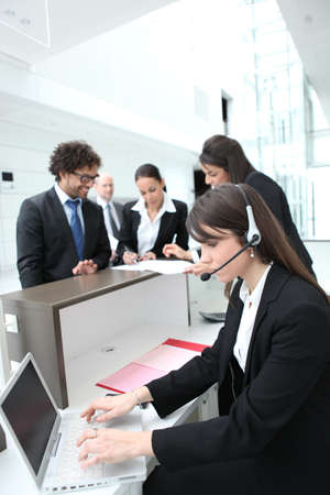 Female receptionist using a headset and laptop computer photo