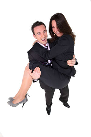man carrying woman: Businessman carrying his partner