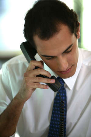 Man in a shirt and tie talking on the telephone Stock Photo - 12019180