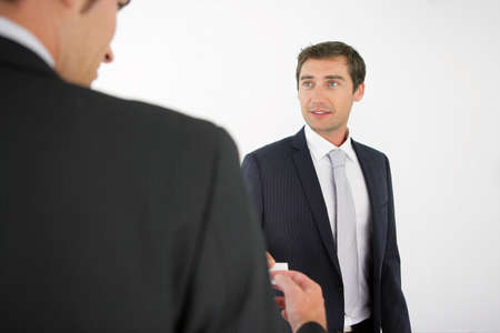 exchanging: Two men exchanging business cards Stock Photo