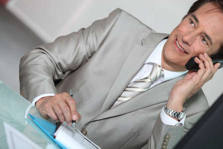 Businessman on the phone smiling Stock Photo - 12019615