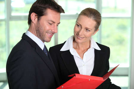 Businessman looking at paperwork with businesswoman. photo