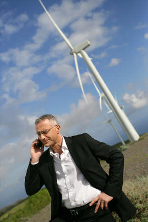 answering call: Man using his cellphone next to wind  turbines Stock Photo
