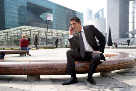 sitting on a bench: Businessman on a call in the city