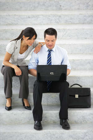 Two business colleagues sat on steps photo