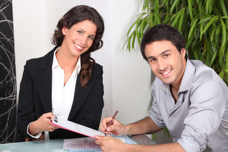 female real estate agent and young man buying house photo