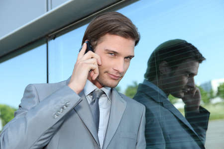 smirk: Slick executive using a cellphone