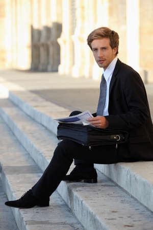 lost city: Businessman sitting on some stone steps Stock Photo