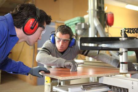 An experienced worker showing an apprentice how to cut a piece of wood using a machine photo