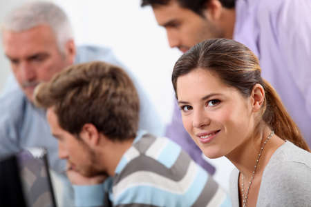 collaborators: Smiling young woman with male colleagues out of focus in the background Stock Photo