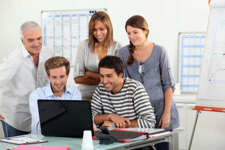gathered: Co-workers gathered around computer screen Stock Photo