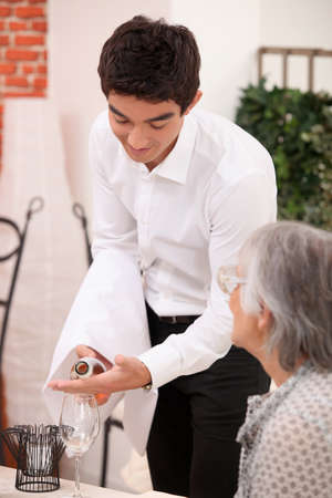 60 64 years: Young waiter serving an older customer rose wine Stock Photo