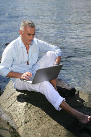 old technology: L'uomo con il suo computer portatile con l'acqua