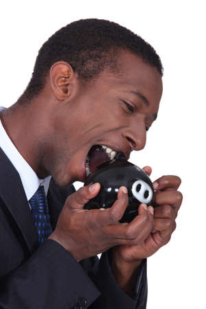 dire: Man trying to bite open a piggy bank Stock Photo