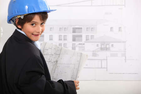 Young boy examining architectural drawings photo