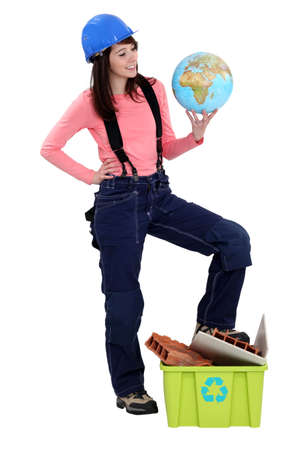 Young female builder holding globe photo