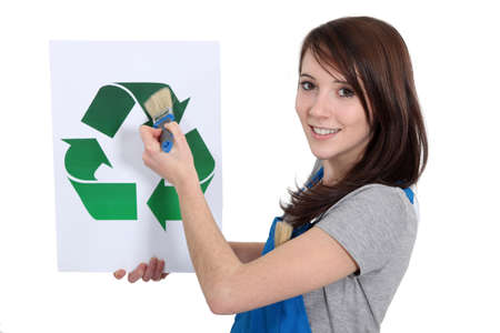 Woman painting recycling symbol photo