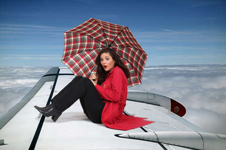 Brunette sat on the wing of an airplane photo