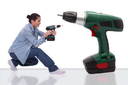 yourselfer: girl with bun holding drill near giant drill