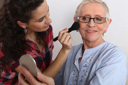 Young woman applying blush on her grandmother photo