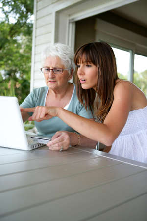 discovering: a grandmother and her granddaughter doing computer Stock Photo
