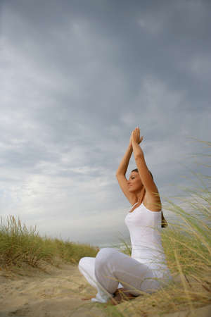 Woman practicing yoga in a field photo