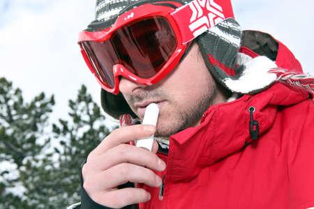 Skier applying lip balm photo