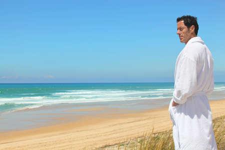 Man in bathrobe on the beach photo