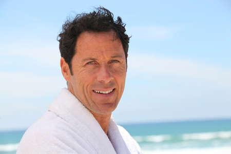 bath gown: Man stood at the beach wearing bath robe
