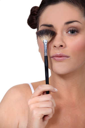 Woman hiding her eye with a brush for makeup photo