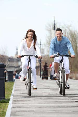 Young couple riding bikes along a boardwalk photo