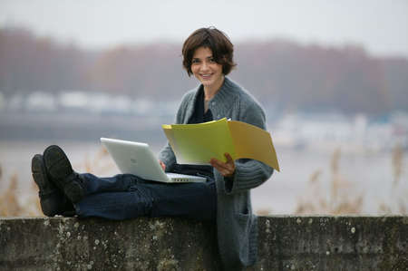 laptop outside: Woman studying whilst sat on a wall