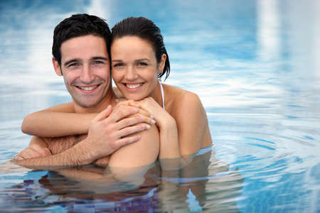 bikini pool: Happy couple hugging in a swimming-pool Stock Photo