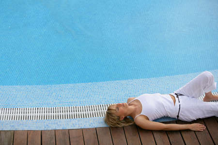 beautiful blonde resting on swimming pool edge photo