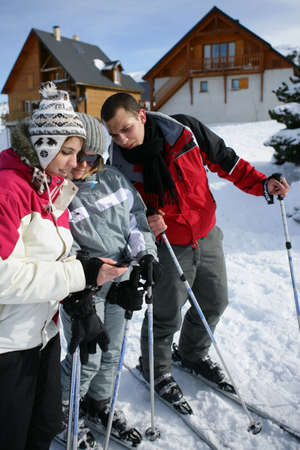 lodging: Ski teenagers looking at a phone Stock Photo