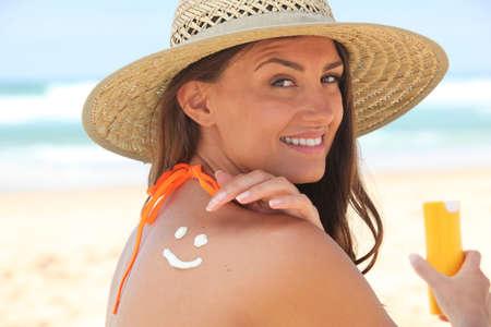 sunbath: Vrouw toepassing zonnebrandcrème op het strand Stockfoto