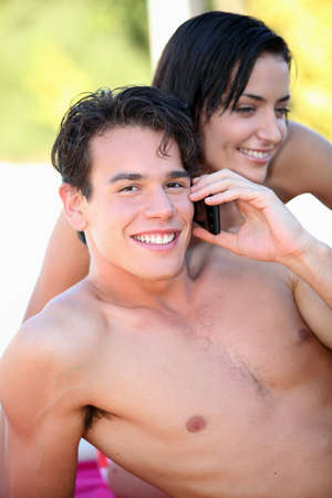 bare-chested boy phoning with girlfriend by his side Stock Photo - 12019406