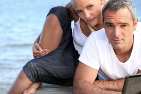 practical: salt-and-pepper guy with laptop posing with younger girlfriend Stock Photo