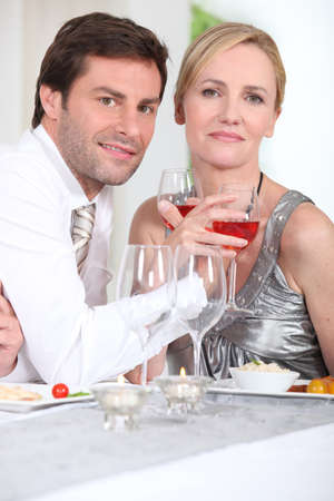 entwined: Romantic couple enjoying rose wine with dinner