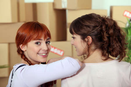 two girlfriends moving into a new apartment Stock Photo - 12019555
